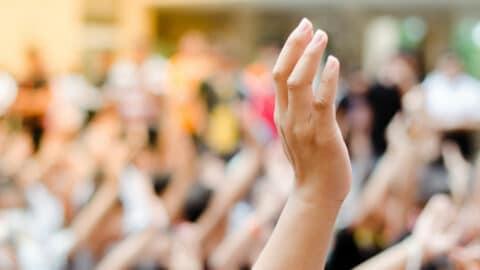 Erhobene Hand in einer Menschenmasse