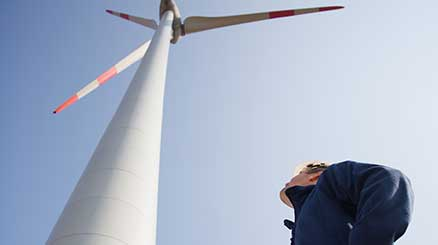 Mann schaut an einem Windrad hoch