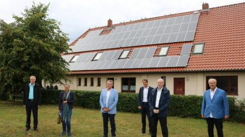 Projektinitiatoren und Energiepolitiker vor dem mit Solarzellen bedeckten Gemeindezentrum von Lübesse.