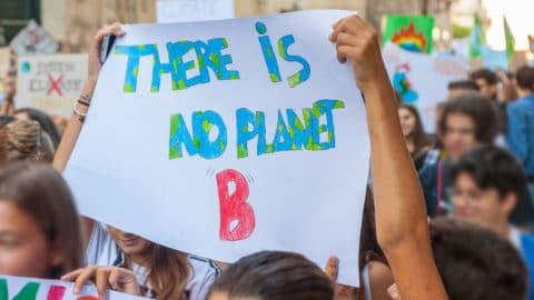 """Junge Demonstranten halten ein selbst gemaltes Plakat mit der Aufschrift """"There ist no planet B"""" hoch"""