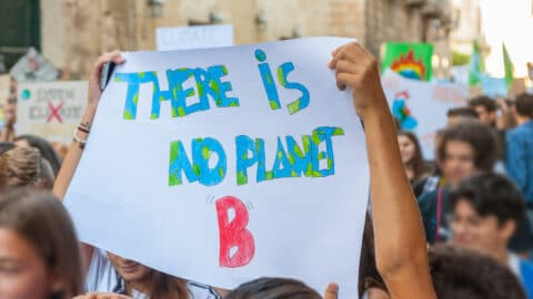 """Junge Menschen halten ein Plakat mit der Aufschrift """"There is noc Planet B"""" hoch."""