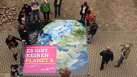 Menschen stehen um Plakat Es gibt keinen Planet B