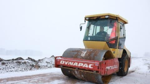 Walze fährt über eine verschneite Baustelle