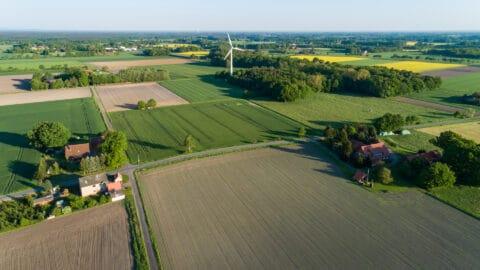 Luftbildaufnahmen Acker, Wiesen, Wald und Einzelgehöften sowie ein einzelnes Windrad.