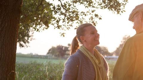 Frau lächelt Mann in der Abendsonne an.