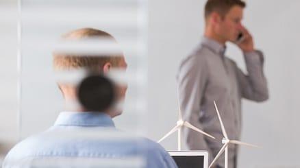 Zwei Männer im Büro, einer am Computer, einer am Telefon