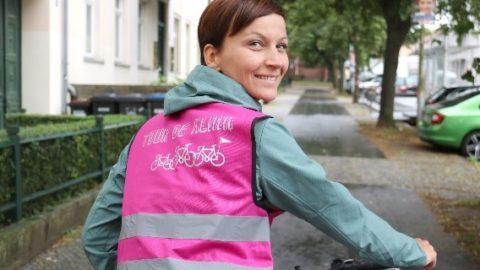 Radfahrerin mit magenta-farbener Weste blickt über die Schulter