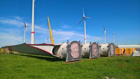Turmteile für Windräder liegen auf der Wiese, vor bereits montierten Windrädern.