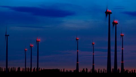 Windräder im Nachthimmel mit rotem Blinklicht