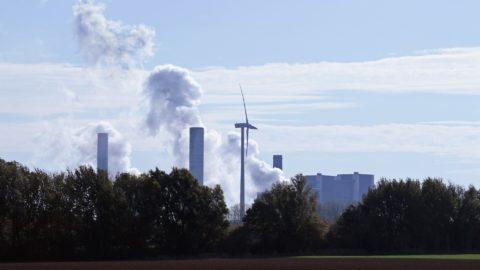 Windrad vor Industrieanlage mit rauchenden Schornsteinen