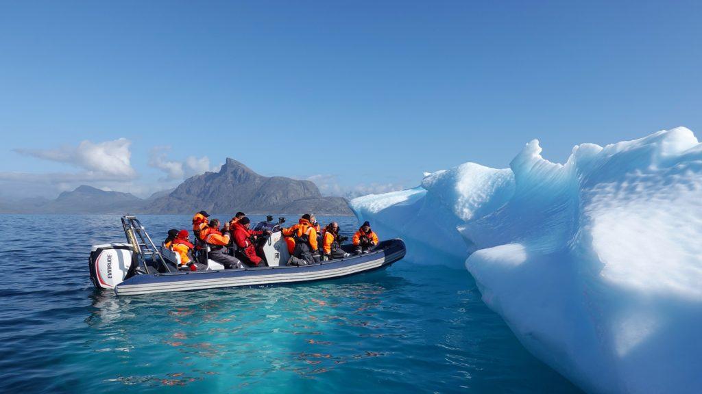 Schlauchboot mit Menschen an einer Eiskante