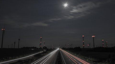 Straße bei Nacht von beleuchteten Windrädern gesäumt